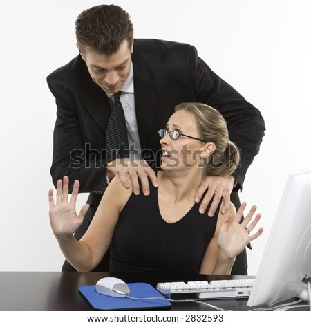 Caucasian mid-adult man sexually harassing woman sitting at computer. - stock photo