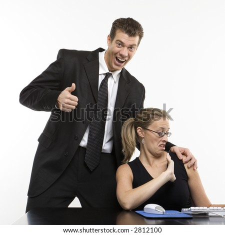 Caucasian mid-adult man sexually harassing woman sitting at computer and giving thumbs up.