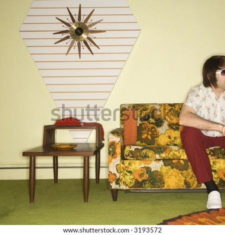 Caucasian mid-adult man sitting on colorful retro sofa wearing sunglasses in room with vintage decor. - stock photo