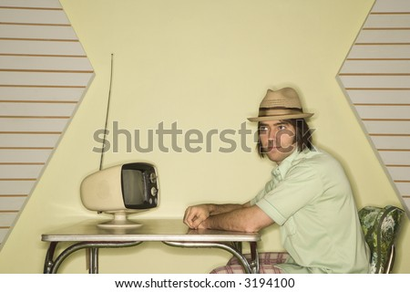 Caucasian mid-adult man wearing hat sitting at 50's retro dinette set in front of old television. - stock photo