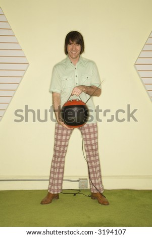 Caucasian mid-adult man wearing vintage clothing holding round red retro television. - stock photo
