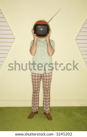 Caucasian mid-adult man wearing vintage clothing holding round red retro television in place of head. - stock photo