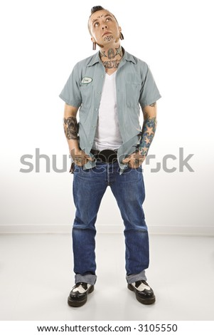 Caucasian mid-adult man with tattoos and piercings. - stock photo