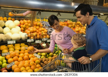 Caucasian mid-adult parents grocery shopping for fruit with male toddler.