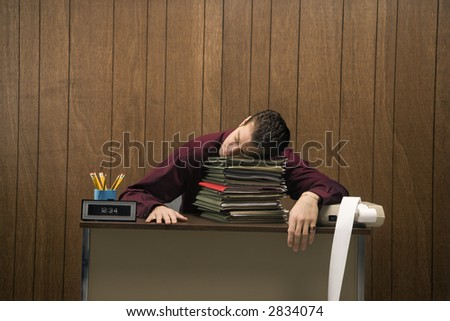 Caucasian mid-adult retro businessman sitting at desk resting his head on a tall stack of folders. - stock photo