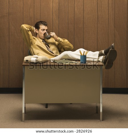 Caucasian mid-adult retro businessman sitting with feet propped on desk leaning back with hand behind head drinking coffee. - stock photo