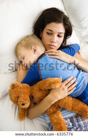 Caucasian mid adult woman holding sleeping toddler in bed. - stock photo