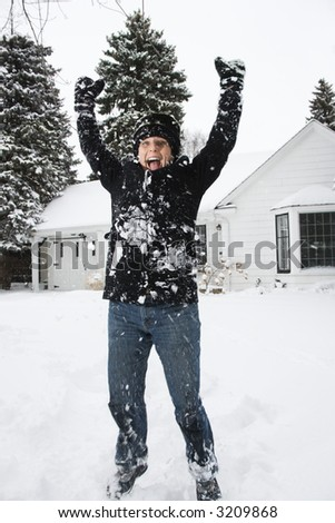 Caucasian mid adult woman jumping in air in snow. - stock photo