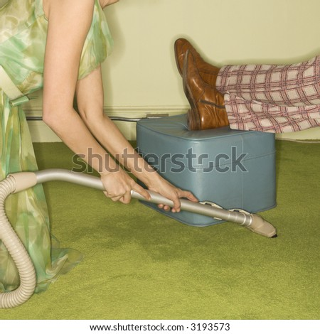 Caucasian mid-adult woman kneeling and vaccuuming carpet around male feet resting on foot stool. - stock photo