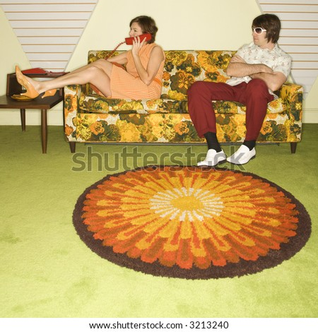 Caucasian mid-adult woman on phone while Caucasian mid-adult man wearing sunglasses watches from sofa. - stock photo