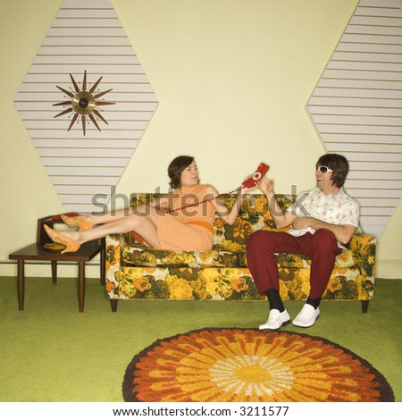Caucasian mid-adult woman passing phone to Caucasian mid-adult man wearing sunglasses sitting on sofa. - stock photo