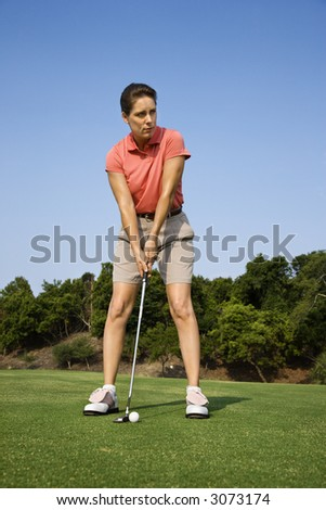 Caucasian mid-adult woman putting golf ball. - stock photo