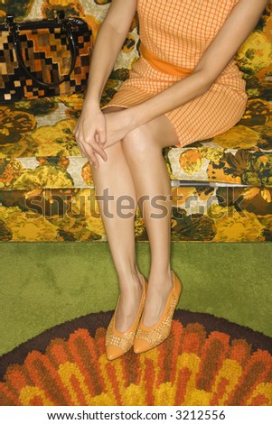 Caucasian mid-adult woman sitting on colorful retro sofa with hands on knee. - stock photo