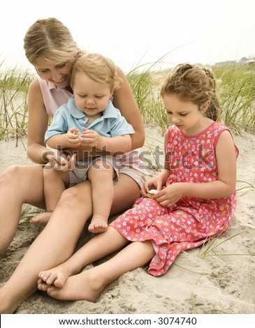 Caucasian mid-adult woman sitting with male toddler on lap and beside Caucasian female child on beach  looking at shells. - stock photo