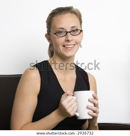 Caucasian mid-adult woman wearing eyeglasses holding coffee cup and looking at viewer.
