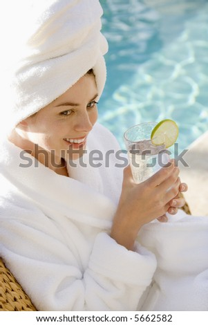 Caucasian mid-adult woman wearing robe and towel on head drinking from glass next to pool.