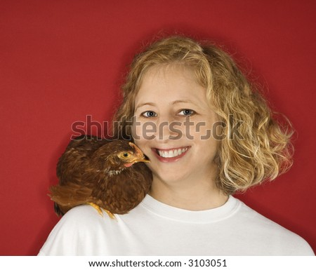Caucasian mid-adult woman with chicken on shoulder.