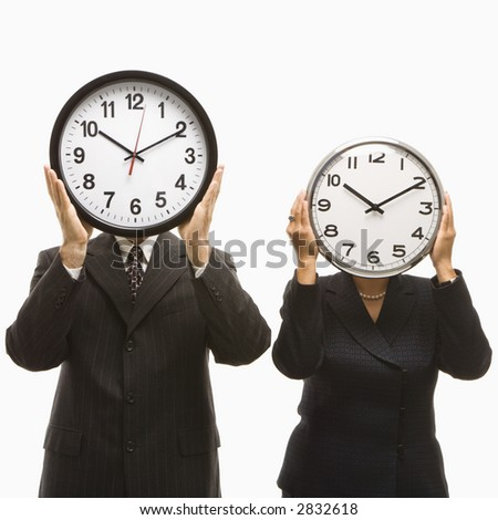Caucasian middle-aged businessman and Filipino businesswoman holding clocks in front of their heads standing against white background. - stock photo