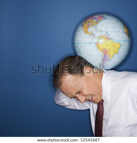 Caucasian middle aged businessman carrying world on shoulders straining. - stock photo
