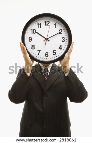 Caucasian middle-aged businessman holding clocks in front of their heads standing against white background.