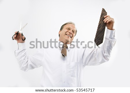 Caucasian middle aged businessman holding cut off necktie and scissors smiling.