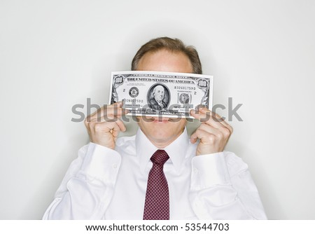Caucasian middle aged businessman holding hudred dollar bill. - stock photo