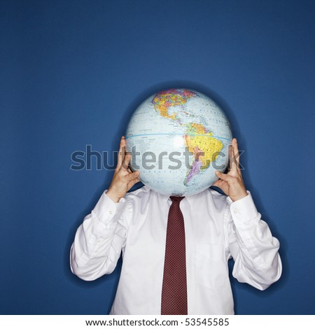Caucasian middle aged businessman holding world globe in front of face.