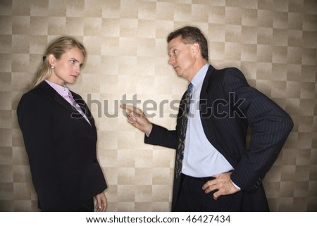 Caucasian middle-aged businessman pointing to and reprimanding mid-adult Caucasian businesswoman. Horizontal format. - stock photo