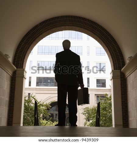 Caucasian middle aged businessman silhouette standing in archway holding briefcase. - stock photo