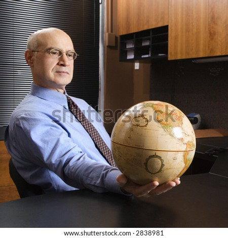 Caucasian middle-aged businessman sitting at desk in office holding globe. - stock photo