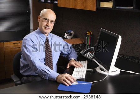 Caucasian middle-aged businessman sitting at desk in office in front of computer.