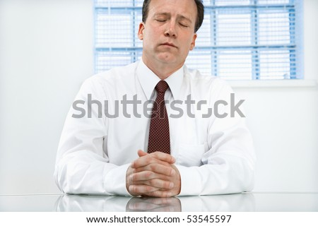 Caucasian middle aged businessman sitting at desk with eyes closed. - stock photo