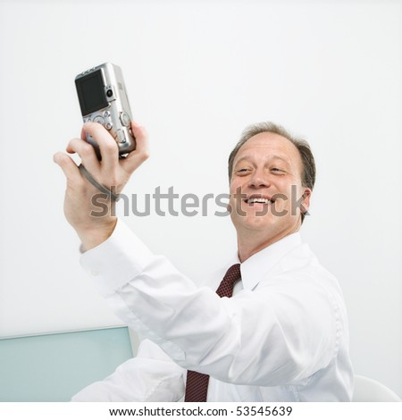 Caucasian middle aged businessman taking picture of himself with camera smiling. - stock photo