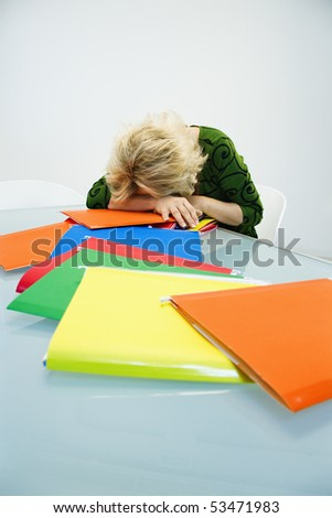 Caucasian middle aged businesswoman sitting at office desk with head down on top of pile of folders. - stock photo