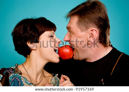 Caucasian middle aged couple eating red apple. Isolated on turquoise - stock photo