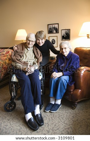 Caucasian middle-aged daughter with elderly parents in retirement community center. - stock photo