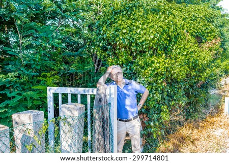 Caucasian middle-aged man, elegant and sporty dressing a blue polo, has a thoughtful look while holding head and leaning against a steel gate in the Italian countryside in summer - stock photo