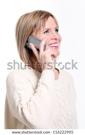 Caucasian middle aged woman on cellphone smiling over white background - stock photo