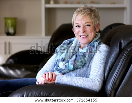caucasian middle aged woman sitting on sofa at home - stock photo