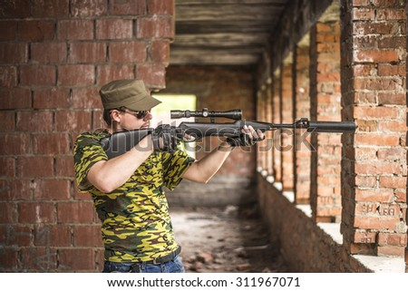 Caucasian military man with sunglasses indoor urban room space stand with rifle with a telescopic sight near abandoned red brick wall with windows. Corridor in perspective.Empty space for inscription  - stock photo