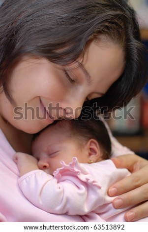Caucasian mother and baby hugging closely