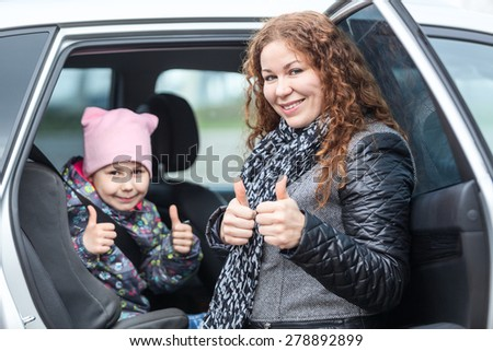 Caucasian mother and child showing thumbs up after seatbelt fastening in car infant chair - stock photo