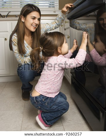 Caucasian mother and daughter kneeling by oven peering in. - stock photo