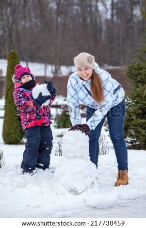 Caucasian mother and daughter making snowman, looking at camera - stock photo