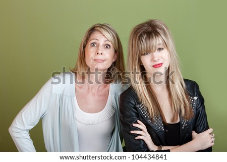 Caucasian mother and daughter over green background making faces - stock photo