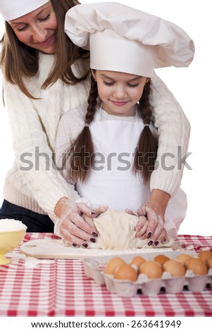 Caucasian mother and daughter preparing dough and having fun, isolated on white background - stock photo