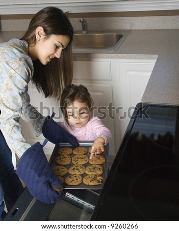 Caucasian mother and daughter  taking cookies out of oven. - stock photo