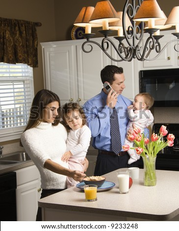 Caucasian mother and father in kitchen busy with children and cellphone. - stock photo
