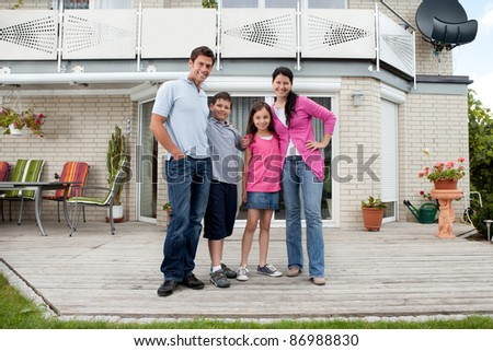 Caucasian mother and father with children standing in front of house
