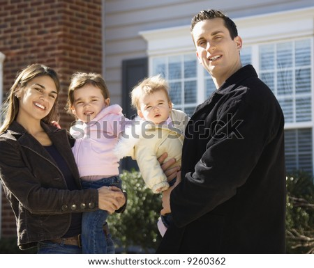 Caucasian mother and father with children standing in front of house. - stock photo
